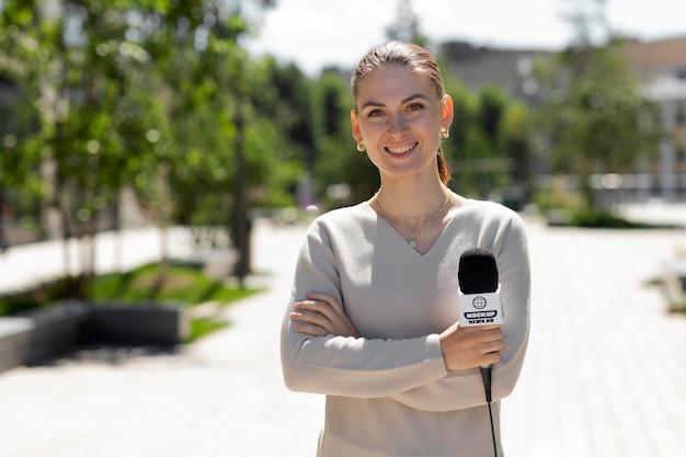 Periodista sosteniendo una maqueta de micrófono