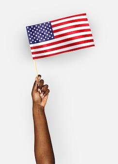 Persona che sventola la bandiera degli stati uniti d'america