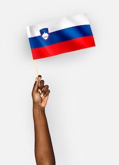 Persona che sventola la bandiera della repubblica di slovenia