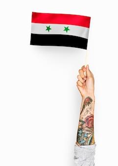 Persona che sventola la bandiera della siria