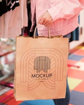 Persona del primo piano che tiene il sacchetto della spesa di mock-up