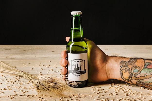 Persona del primo piano che tiene una bottiglia di birra