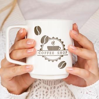 Persona in possesso di tazza bianca mock-up