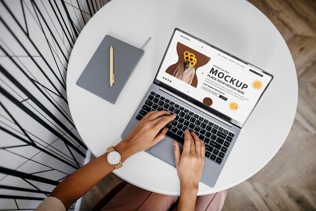 Persona en lugar moderno usando maqueta de laptop