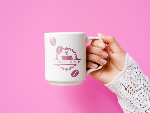 Persona con maqueta de taza blanca sobre fondo rosa
