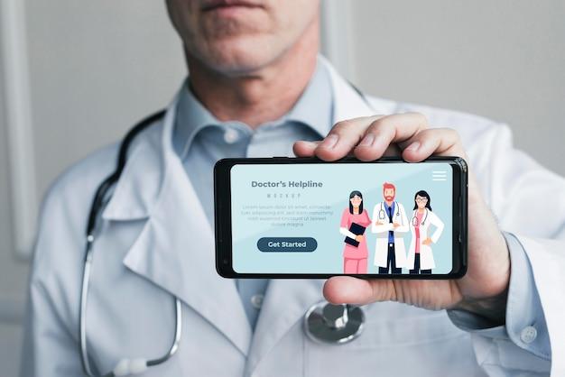 Persona que tiene la página de inicio de la línea de ayuda del médico en el teléfono móvil