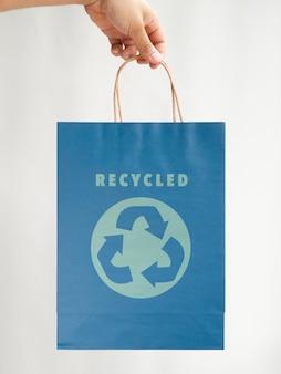 Persona sosteniendo una bolsa de papel azul