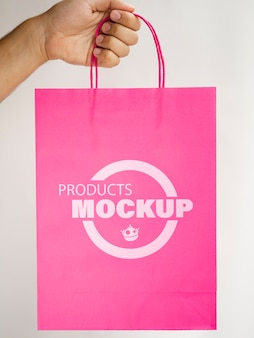Persona sosteniendo una bolsa de papel rosa