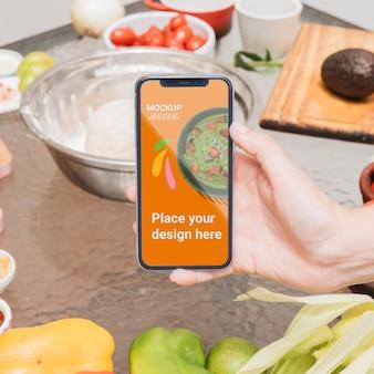 Persona sosteniendo una maqueta de comida saludable de teléfono móvil