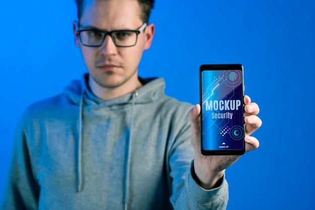Persona sosteniendo una maqueta de seguridad digital de teléfono móvil