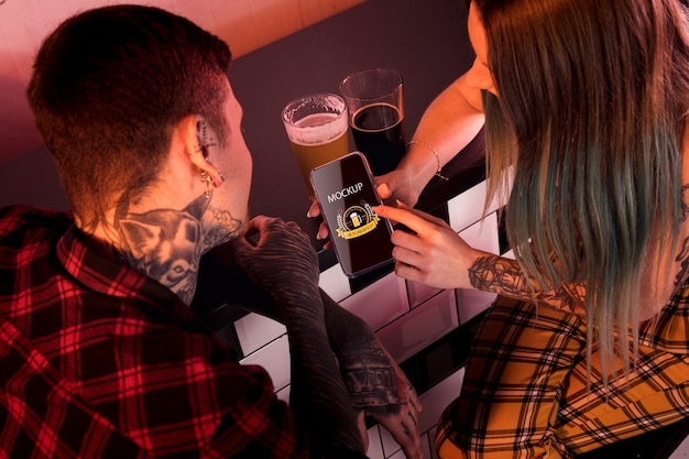 Personas de alto ángulo con maqueta de cerveza y teléfono