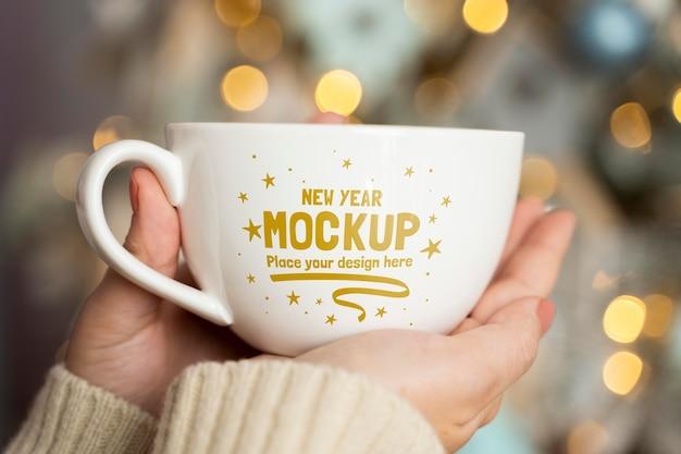 Persoon bedrijf cup met onscherpe kerstboom