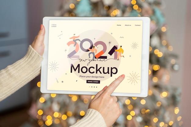 Persoon bedrijf tablet naast kerstboom met nieuwjaar