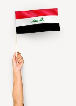 Persoon die de vlag van de republiek irak zwaaien