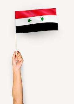 Persoon die de vlag van syrië zwaaien