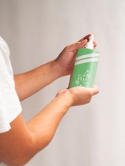 Persoon die een fles vloeibare zeep houdt