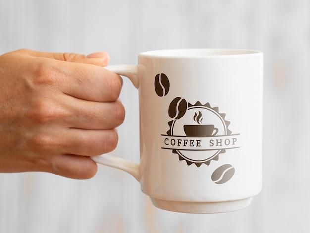 Persoon die een koffiemok houdt