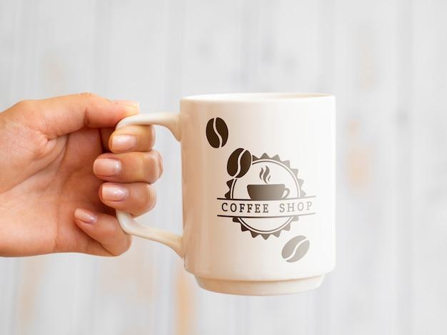 Persoon die een koffiemok steunt
