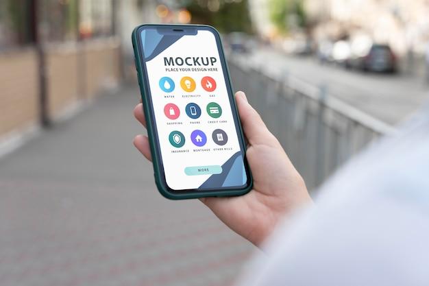 Persoon die een mock-up-smartphone vasthoudt