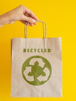 Persoon die een recyclebare papieren zak houdt