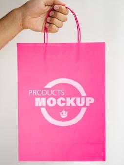 Persoon die een roze papieren zak houdt