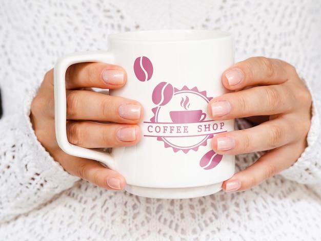 Persoon die het witte model van de koffiemok houdt
