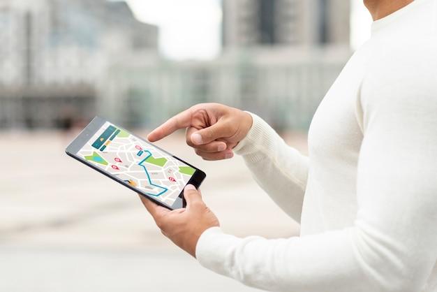 Persoon die in openlucht op kaart van een tablet kijkt