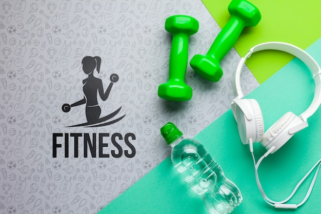 Pesas fitnes con auriculares y botella de agua.