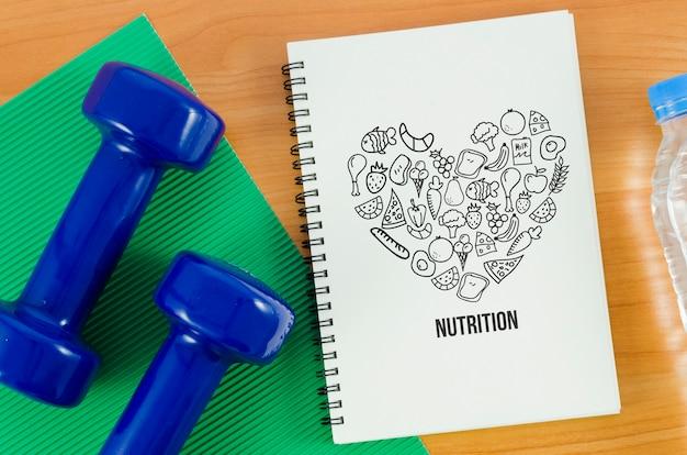 Pesas de manos al lado del cuaderno