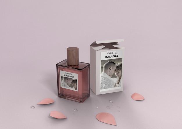 Pétalos y botella de perfume en la mesa
