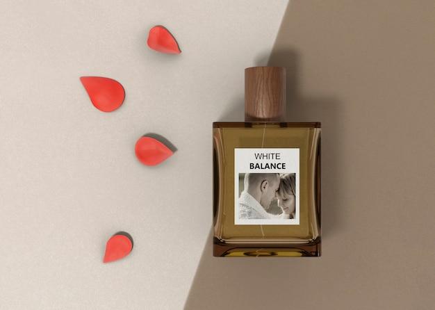 Pétalos de flores junto a la botella de perfume