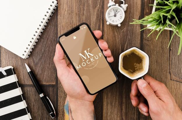 Piatto laici mani che tengono smartphone mock-up e caffè