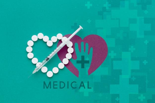 Pillole a forma di cuore e siringa