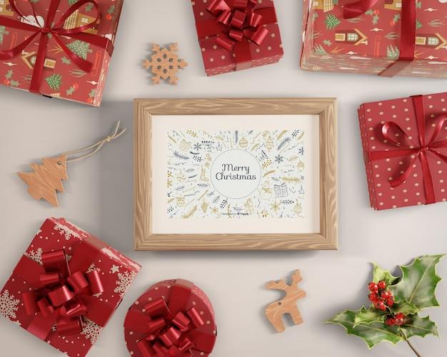 Pintura con tema navideño rodeada de regalos