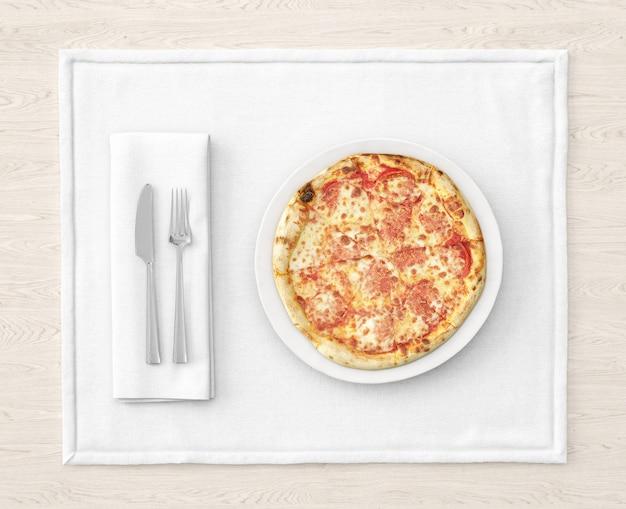 Pizza en plato blanco con cubiertos