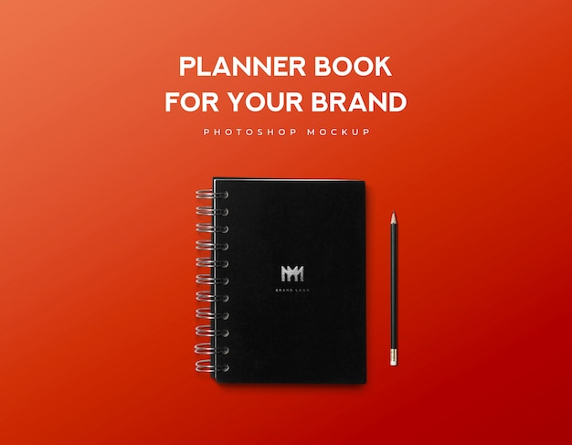 Planificador de libro para su marca y lápiz negro sobre fondo rojo.
