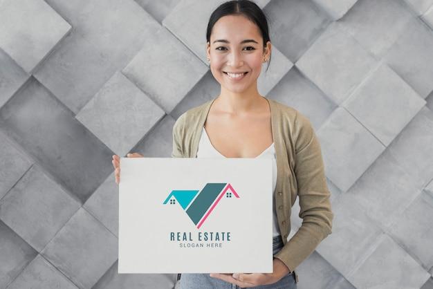 Plano medio de mujer sosteniendo un cartel con bienes raíces