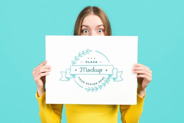 Plano medio de mujer sosteniendo una tarjeta de maqueta de papelería