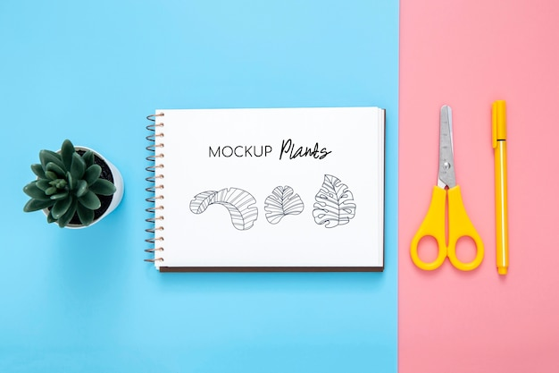 Plano de la superficie del escritorio con bloc de notas y tijeras