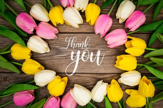 Plantilla de saludo con tulipanes sobre un fondo de madera