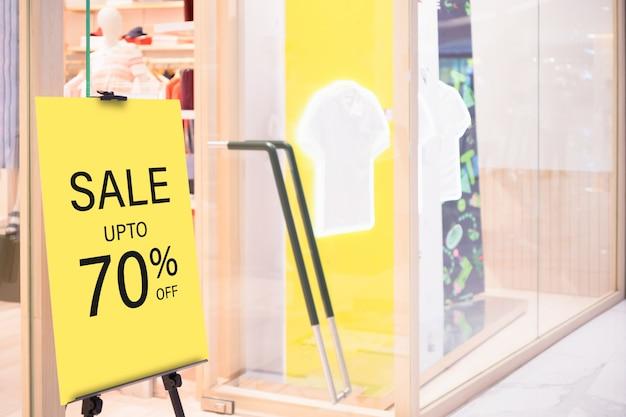 Plantilla de soporte de billbord de etiqueta de venta de maqueta frente a tienda de ropa