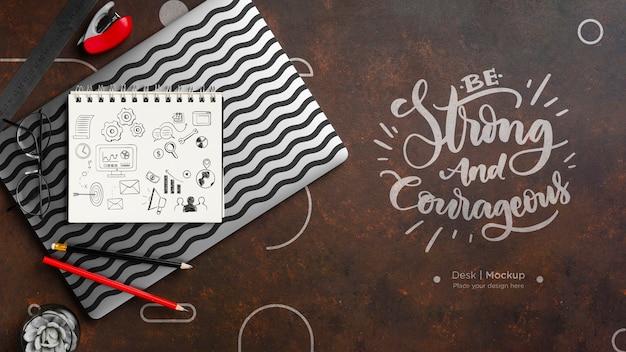 Plat bureauoppervlak met notitieboekje en potloden Gratis Psd