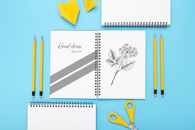 Plat bureauoppervlak met notitieboekjes en potloden