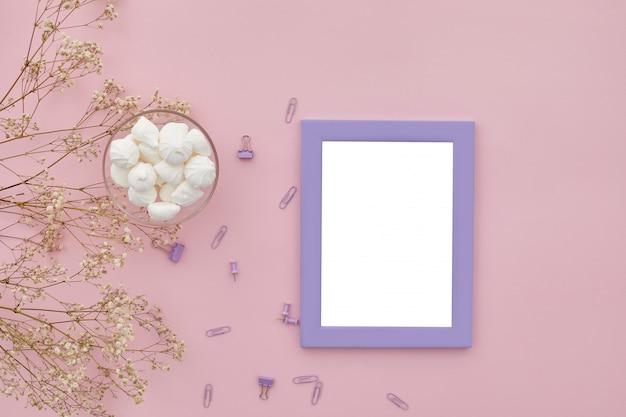 Plat lag bloemen, fotolijst op roze tafel