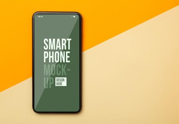 Plat lag, bovenaanzicht van oranje bureau met smartphone mockup sjabloon voor uw ontwerp.