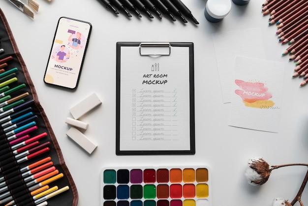 Plat lag kunstenaarspalet en penseel naast klembord