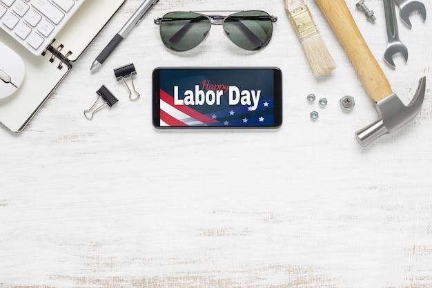 Plat lag mockup smartphone met happy labor day usa holiday en essentiële hulpmiddelen voor werknemers