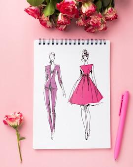 Plat lag notebookmodel en pen in de buurt van rozenboeket