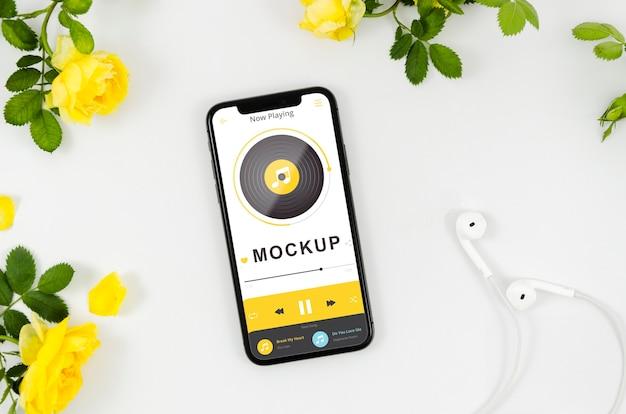 Plat lag smartphone mock-up met bloemen en oortelefoons