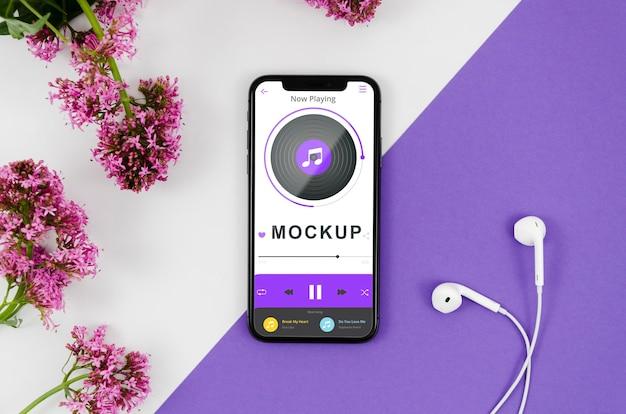 Plat lag smartphone mock-up met oortelefoons en bloemen